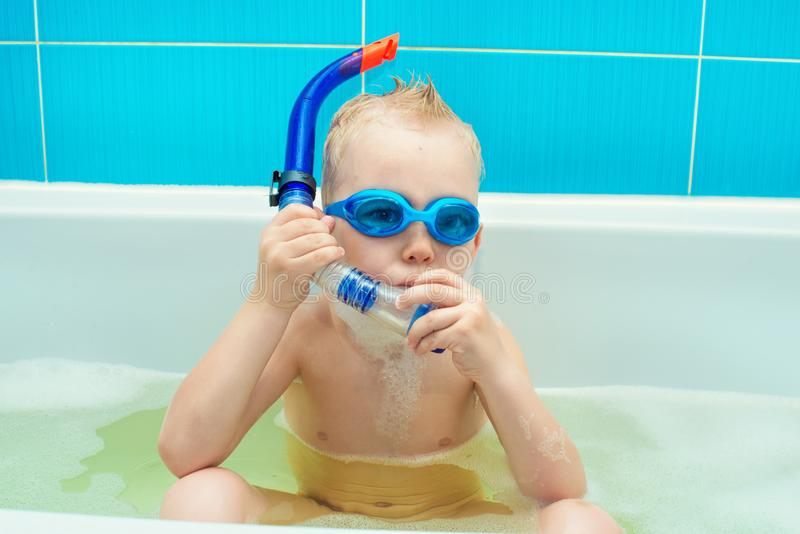 A little boy is floats in goggles and snorkel and playing in the bathroom. royalty free stock images