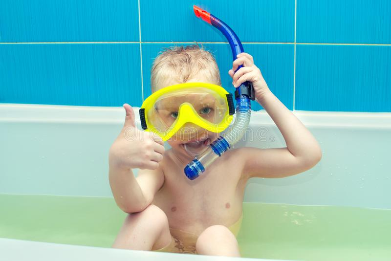 A little boy is floats in mask and snorkel and playing in the bathroom. royalty free stock images