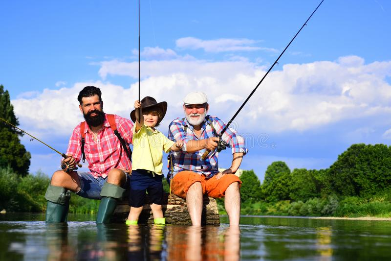 Little boy fly fishing on a lake with his father and grandfather. Summer day. Happy grandfather, father and grandson royalty free stock photos