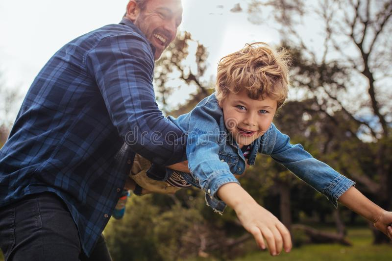 Little boy flying in arms of his dad royalty free stock images