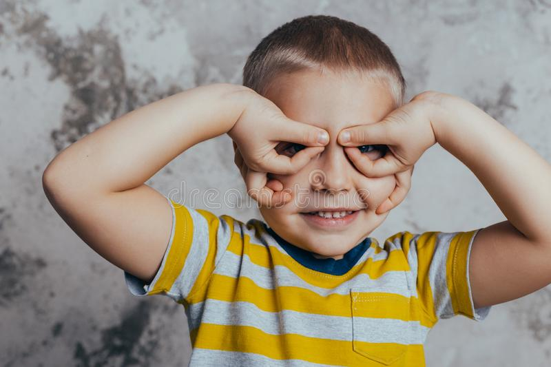 A little boy folded his arms by the eyes posing in front of a gray concrete wall. Portrait of a smiling child wearing a yellow royalty free stock images