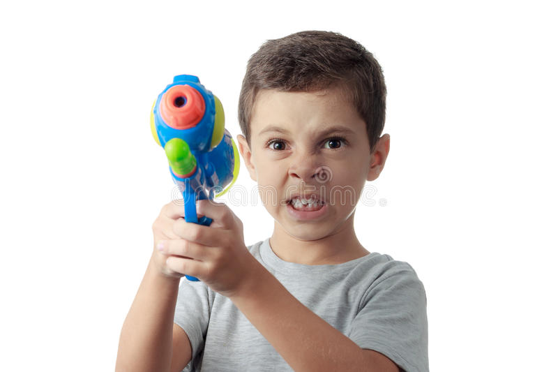Little boy with funny expression playing with water gun. Little boy with funny expression playing with plastic water gun isolated on white royalty free stock photography