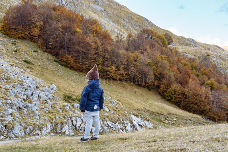 Little boy in funny hat looking at the Durmitor mountains, Monte stock photography