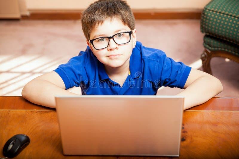Little Boy genom att använda en bärbar dator arkivbilder