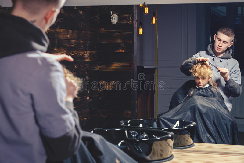 Download Little Boy Getting Haircut By Barber Stock Photo - Image of deadpan, hairstylist: 83704776