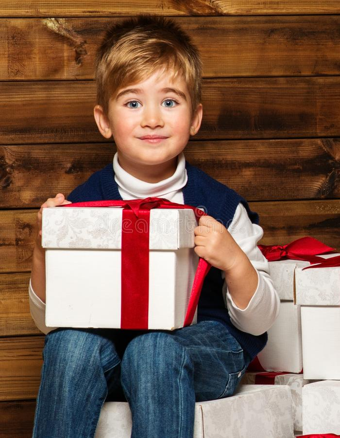 Little boy with gift box. Sitting on gift boxes in wooden house interior royalty free stock photos