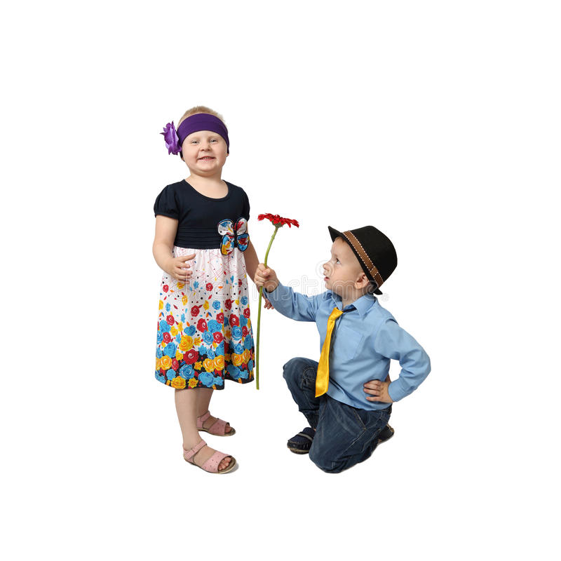 Little boy gifts flower to girl. Boy in country style festive clothes kneeling gifts flower to girl with proud facial expression on white background in square royalty free stock photo