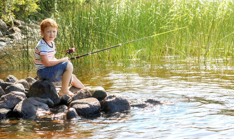 Little boy with ginger hair is fishing on the lake. Sunny summer day. Texture of water surface. Stones. Pier beach.  stock photos