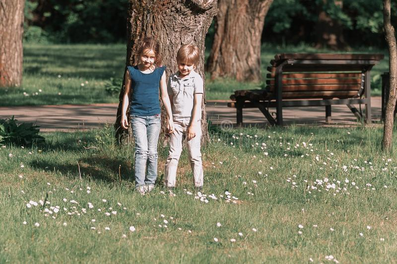 Little boy and girl brother and sister standing next to a big old tree. stock image