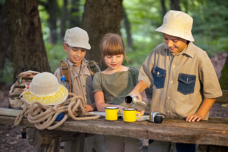 Little boy and girl on camping trip. Children share tea from a thermos bottle,on camping break stock photos