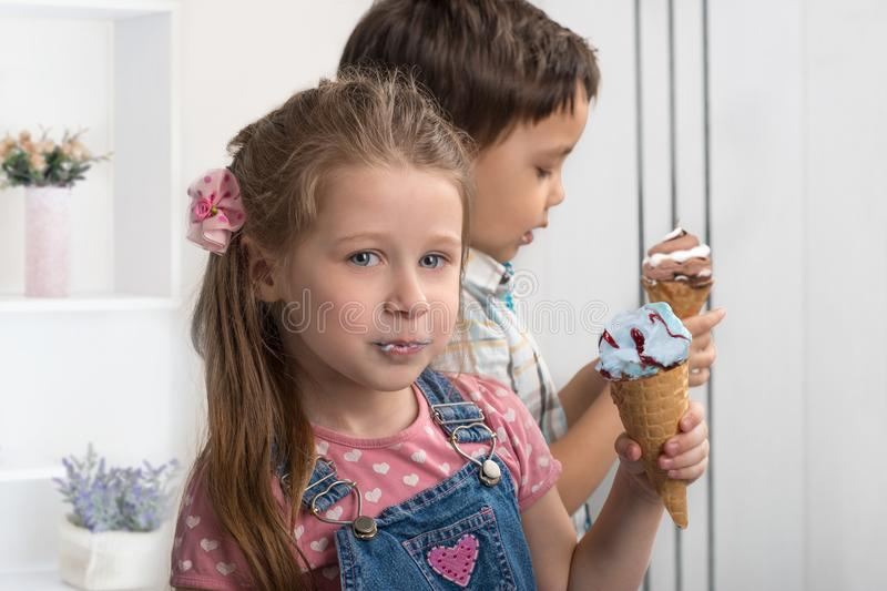 The little boy and girl cheerfully eat ice cream in wafer gun. Close up emotional portrait of the smiling of the little boy and girl . They cheerfully eat ice royalty free stock photos
