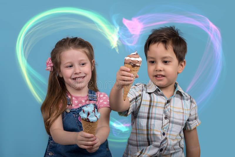 The little boy and girl cheerfully eat ice cream in wafer gun. Close up emotional portrait of the smiling of the little boy and girl on blue background in studio stock photo