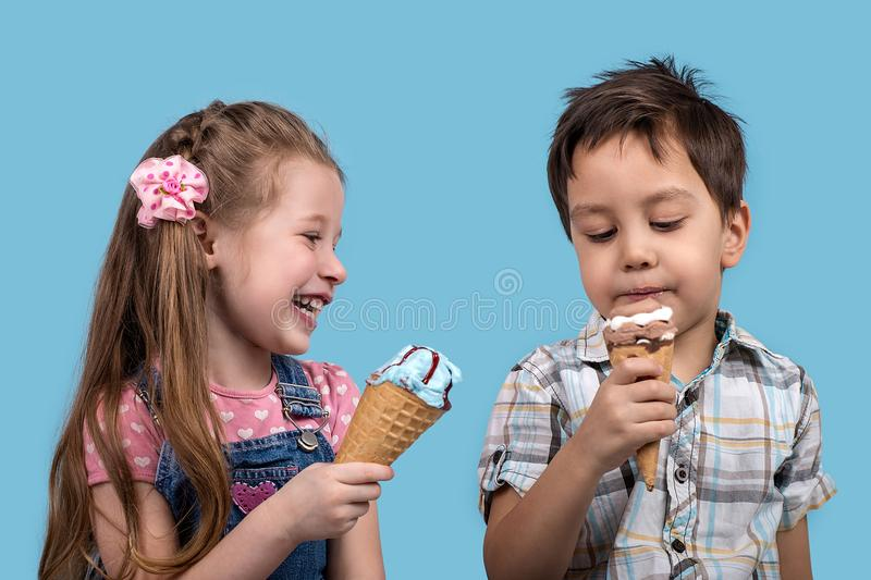 The little boy and girl cheerfully eat ice cream in wafer gun. Close up emotional portrait of the smiling of the little boy and girl on blue background in studio royalty free stock photography