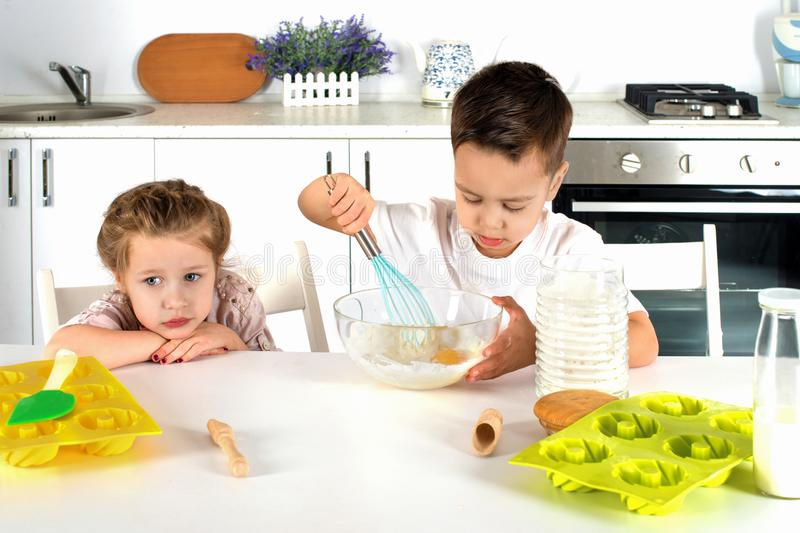 Little boy and girl cook cake in kitchen. Attractive boy and girl cook cake in kitchen stock photos