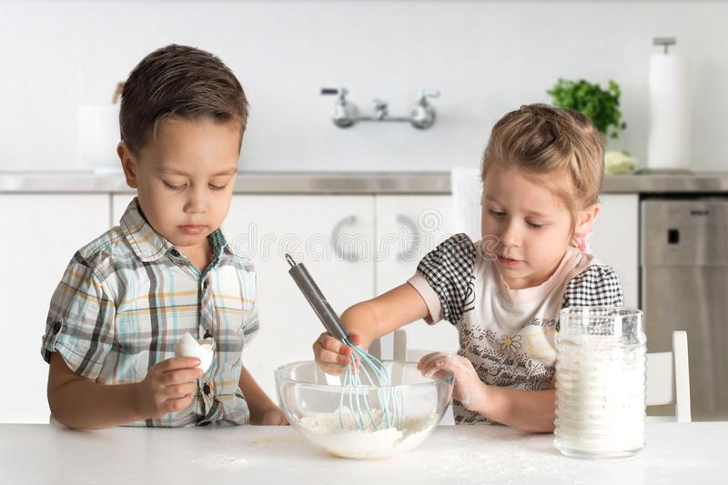 Little boy and girl cook in kitchen. Little boy and girl cook cake in kitchen royalty free stock image