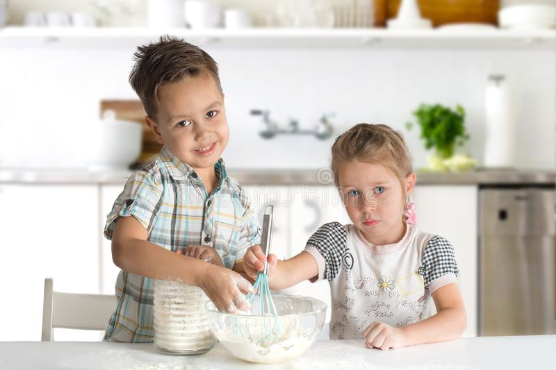 Little boy and girl cook in kitchen. The girl interferes with a nimbus dough, and the boy pours flour to a cup royalty free stock photos