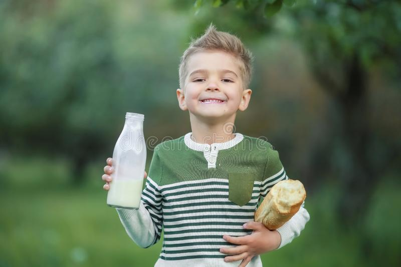 Little boy with girl drink milk and eat a loaf of bread on a haystack in a village at sunset royalty free stock photo