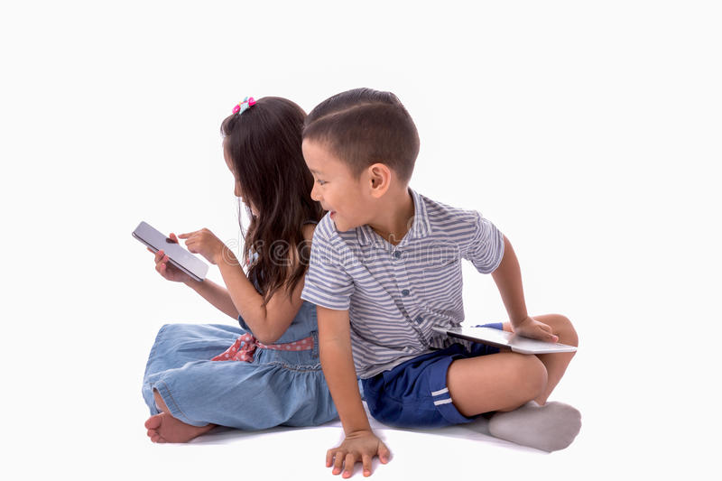 Little boy and girl enjoy playing and learning with smartphone or internet gadget sitting on white floor isolated on white. Little boy and girl enjoy playing and stock image