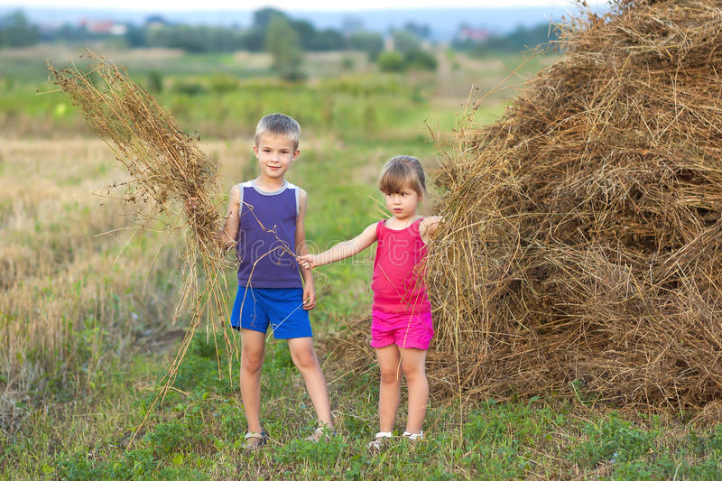 Little boy and girl on field near haystack royalty free stock photography