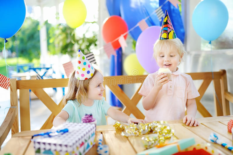 Little boy and girl having fun and celebrate birthday party with colorful decoration and cakes stock photos