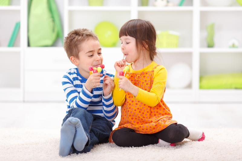 Little boy and girl eating lollipop royalty free stock photography
