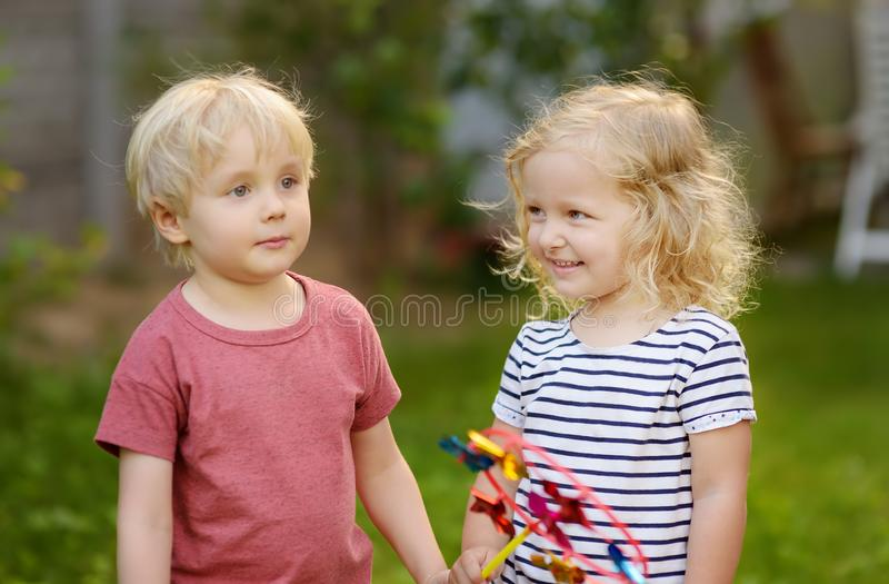 Little boy and girl having fun during walk. Happy kids with pinwheel royalty free stock images