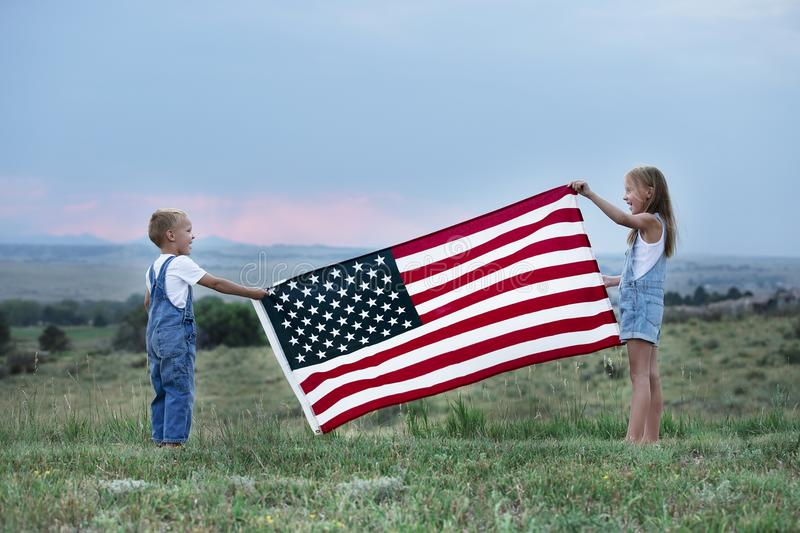 Little boy and girl holding American flag 4th of July independence day stock photos