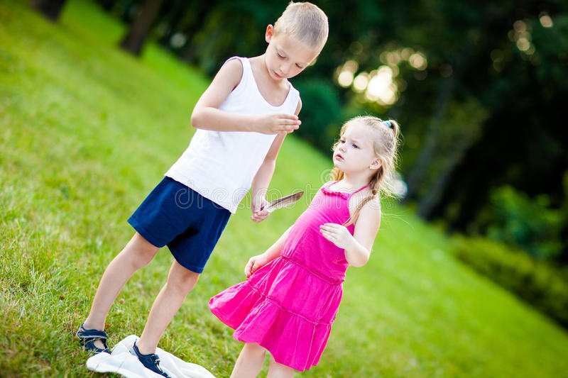 Little boy and girl with ladybird in park stock image