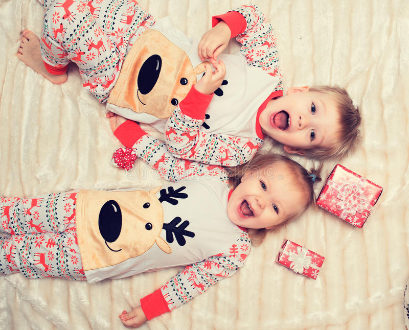 Little boy and girl lie on the bed in pajamas. stock photos