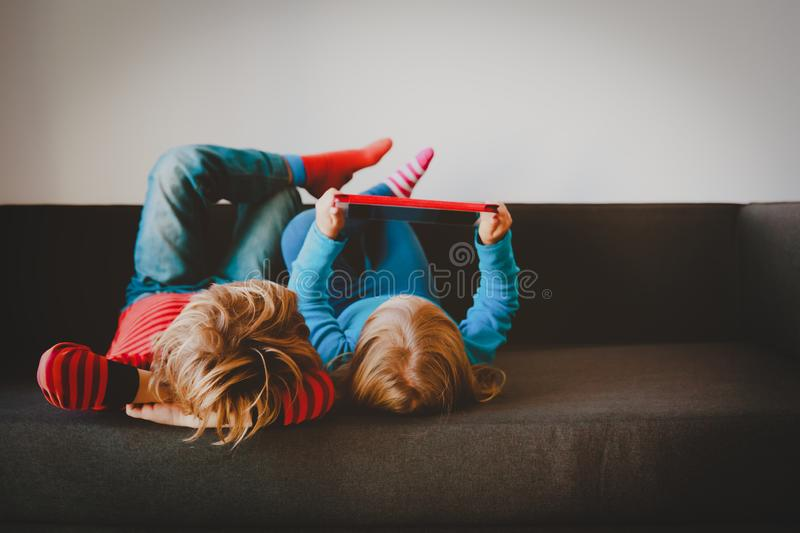 Little boy and girl looking at touch pad at home royalty free stock photography