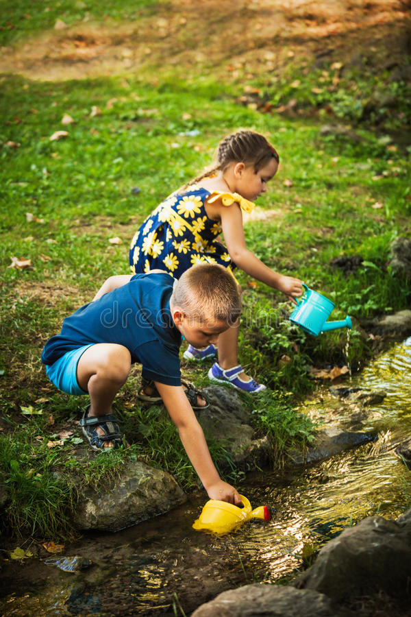 Little boy and girl play draw water in bucket from stream stock image