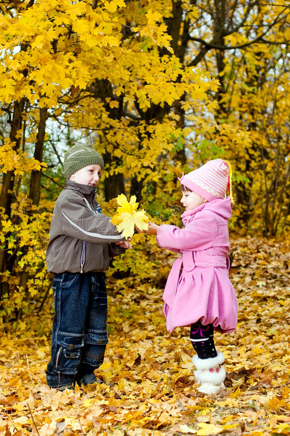 Little boy and girl play in a park in autumn