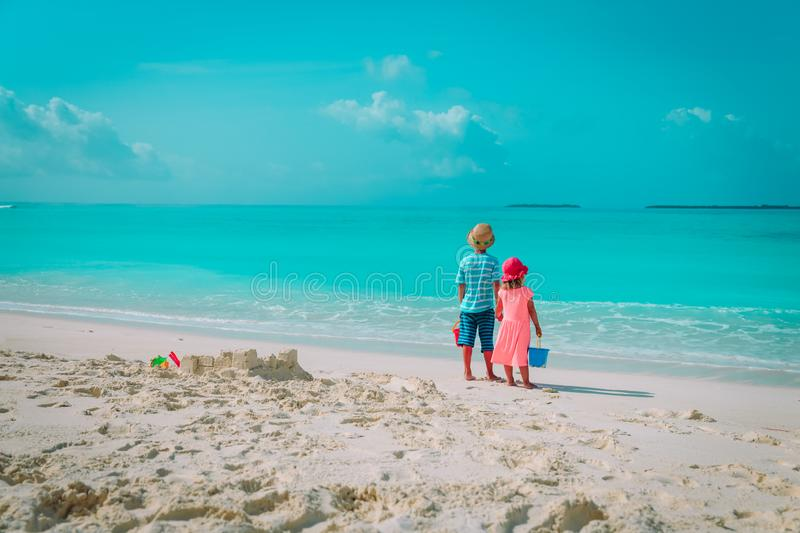 Little boy and girl play with sand on beach stock photos