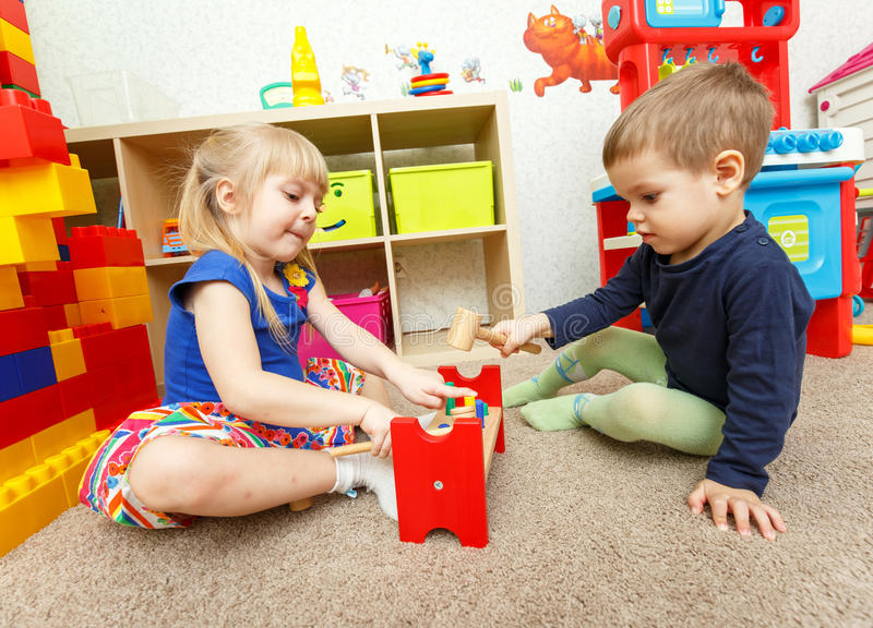 Little boy and girl play with toy hammer in kindergarten stock images