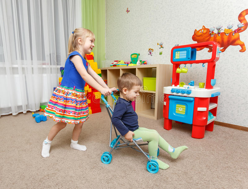 Little boy and girl play with toy stroller at home stock photo