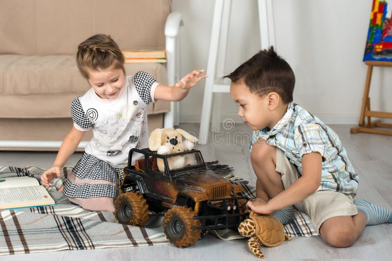 Little boy and the girl play toys. On the floor in the room stock image