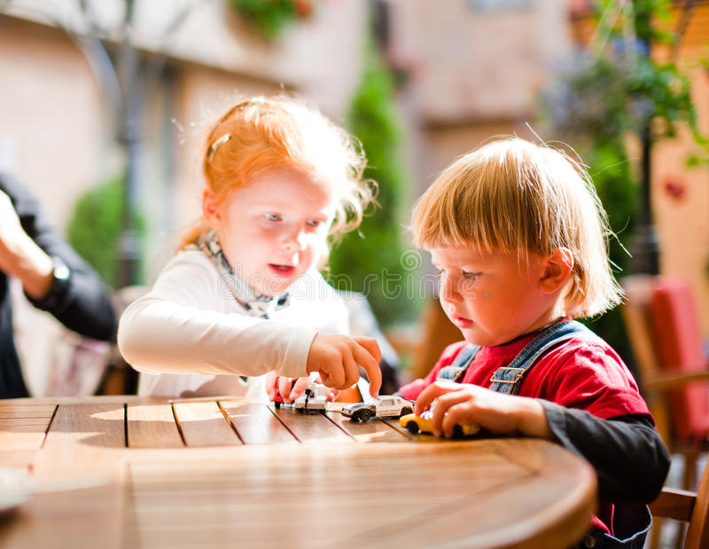 Little boy and girl playing. Little boy ant girl playing on table with toy cars royalty free stock photography