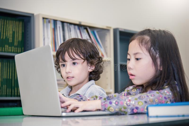 Little boy and girl playing computer games. Small boy and girl tying with laptop stock image