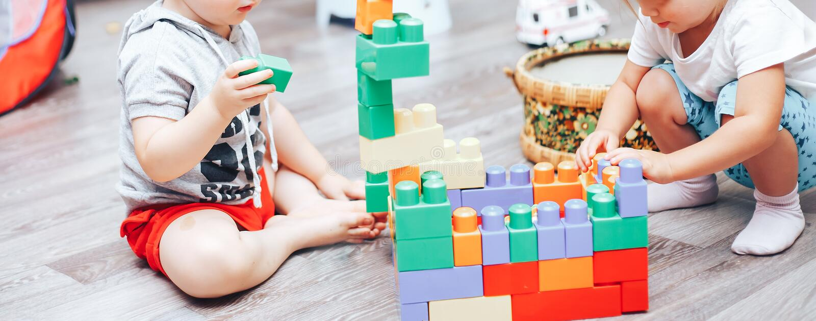 little boy and girl playing toys at home stock photos