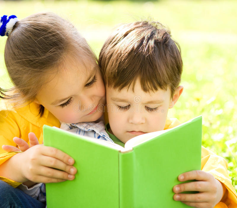 Little boy and girl is reading book royalty free stock image