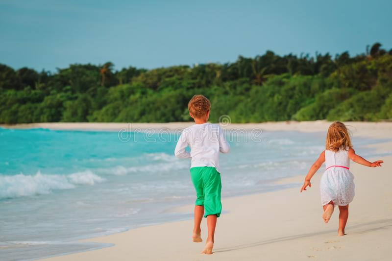 Download Little Boy And Girl Run On Beach Stock Photo - Image of holiday, children: 114288648