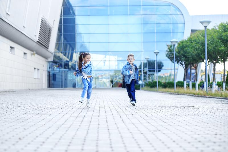 Little boy and girl run down the street. The concept of childhood, family, education. And school royalty free stock photography