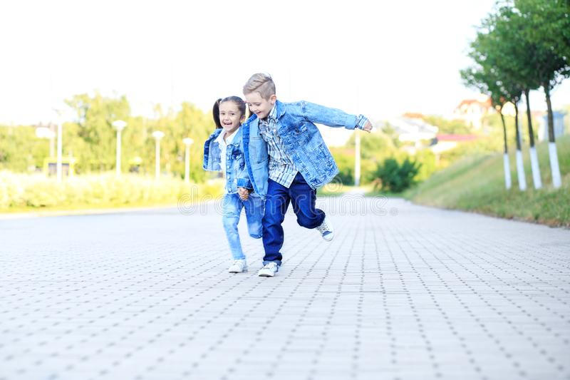 Little boy and girl run, holding hands. The concept of childhood, family, education. And school royalty free stock photo
