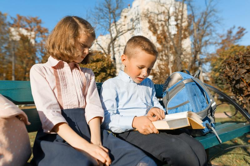 Little boy and girl schoolchildren read a book, sit on a bench, children with backpacks, bright sunny autumn day royalty free stock image
