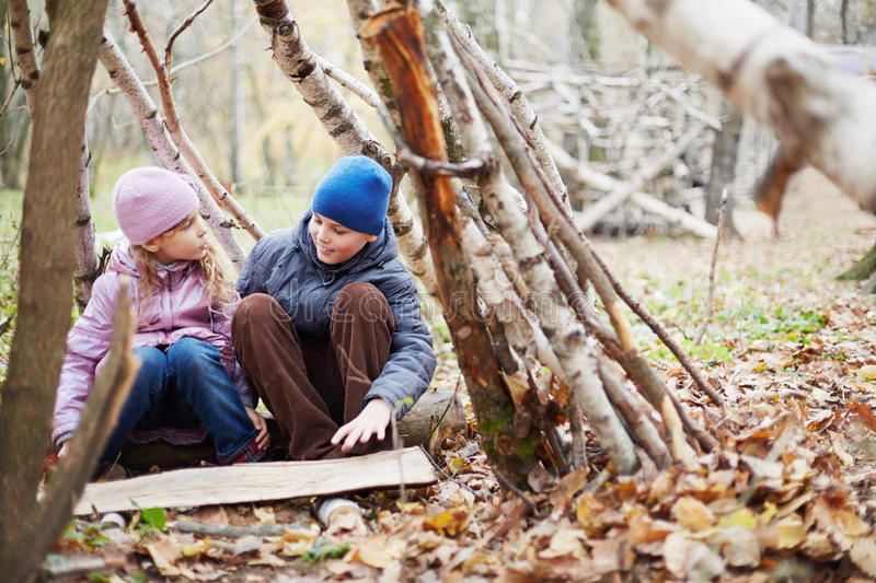 Little boy and girl sit in hut built between birches stock image
