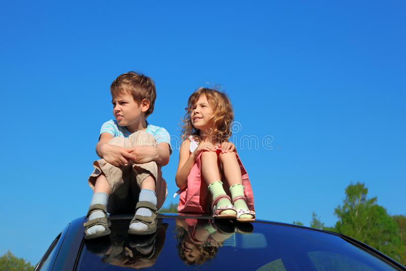 Little Boy And Girl Sitting On Car Roof Royalty Free Stock Image