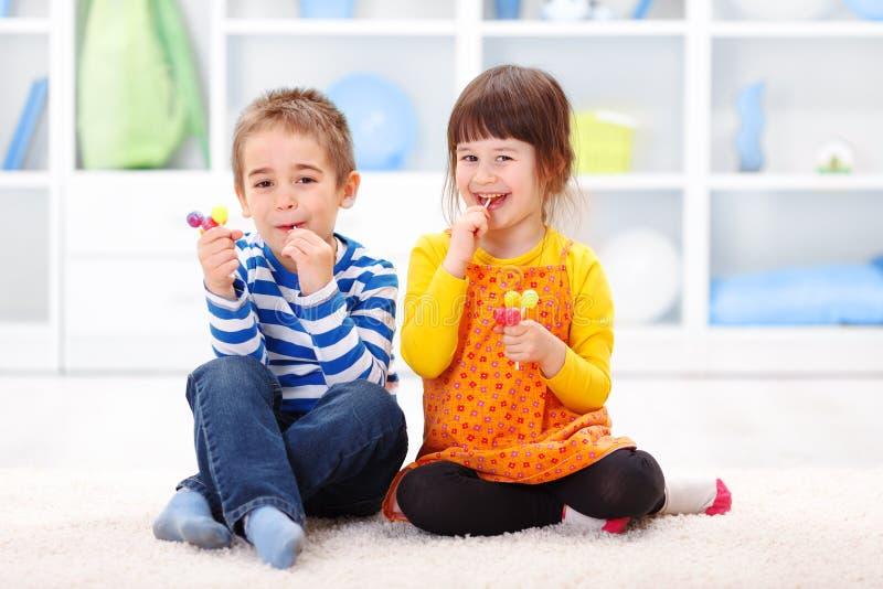 Little boy and girl eating lollipop stock image