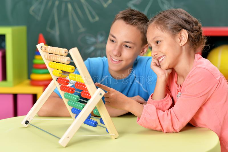 Little boy and girl sitting at table and counting on abacus royalty free stock photo