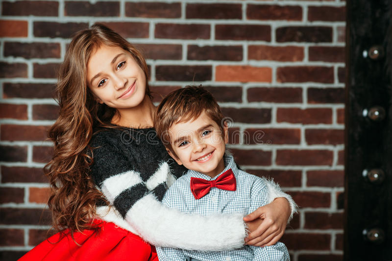 Little boy and girl smiling and hugging on brick background in fashion clothing. Kids brother and sister are happy stock photos