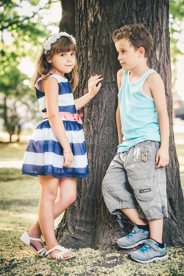 Little boy and girl standing next to the tree stock images